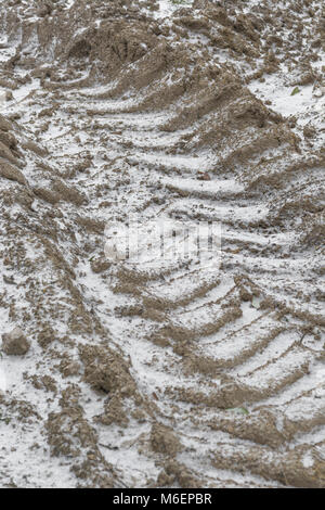 Tractor tyre marks infilled with snow during the 2018 'Beast from the East' cold snap. - Stock Image