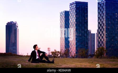 Businessman sitting outdoors at sunset - Stock Image