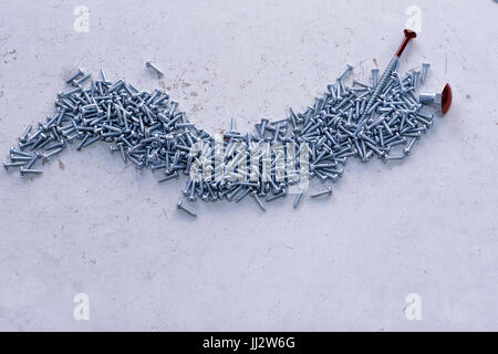 Nail made of screws with red bolt - Stock Image