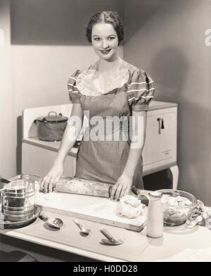 Woman rolling dough on kitchen counter - Stock Image