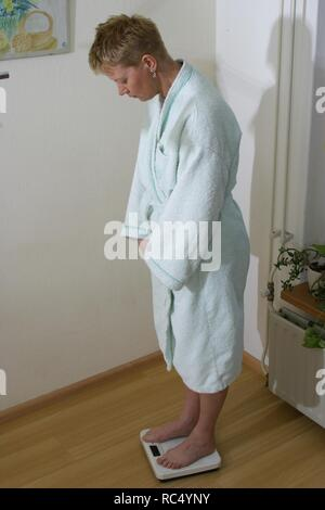 Over 40 woman weighing her self at home in morning dress on scales. - Stock Image