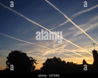 Early morning rush hour in the skies above Sussex, England. Airplane jet streams in all lanes. - Stock Image