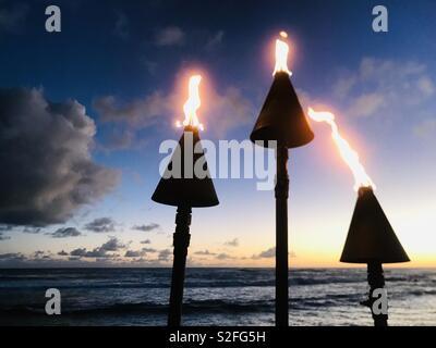Tiki torches at sunset on the beach at a resort. Poipu, Kauai USA. - Stock Image