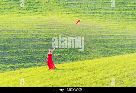 San Quirico d'Orcia, Orcia valley, Siena, Tuscany, Italy. A young woman in red dress  is throwing her hat in a wheat field - Stock Image