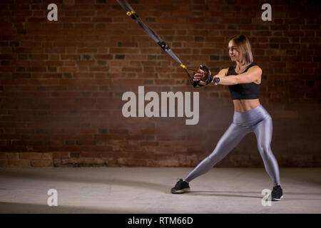 Crossfit female instructor doing full body TRX session workout in gym with red brick walls. - Stock Image