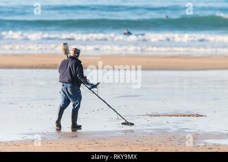 A metal detectorist searching on the beach at Fistral in Newquay in Cornwall. - Stock Image