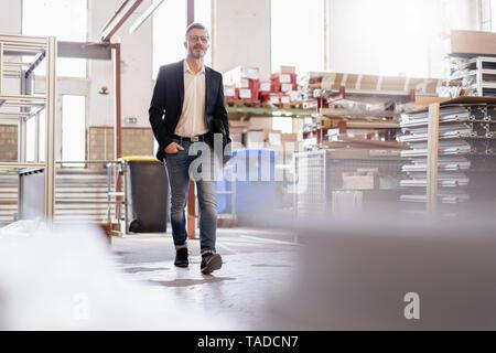 Businessman walking in factory warehouse - Stock Image