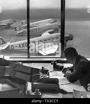 Office in the administrative wing of Tempelhof Airport. On the apron are Lufthansa aircrafts of the type Ju52. The front engine with the tail number D-AXOS bears the name of the fighter pilot Oswald Boelcke. - Stock Image