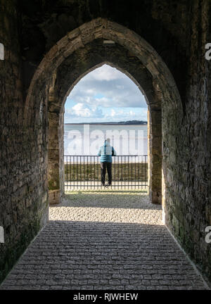 A woman looking out towards the Menai Straits in North Wales from an arch in Caernarfon. - Stock Image
