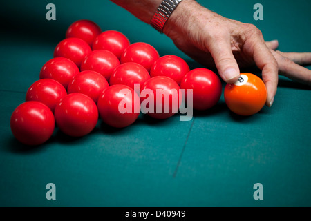 A man sets billiards balls in place before a game of snooker. - Stock Image