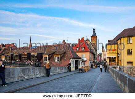 As evening approaches, people dine, chat and stroll on the Alte Mainbrücke in Würzburg, Germany, Würzburger - Stock Image