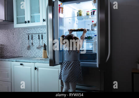 Rear View Of Girl Try To Take Muffins From Refrigerator In Kitchen - Stock Image
