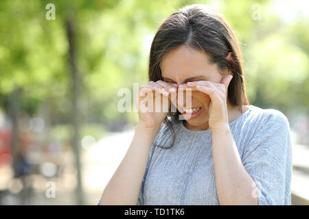 Disgusted woman rubbing her eyes standing outdoors in a park - Stock Image