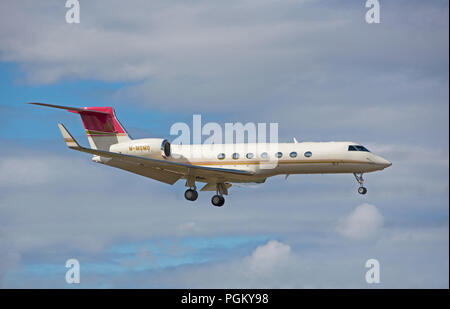 A Jersey registered Gulfstream 550 registration M-MOMO making its final approach into Inverness Dalcross Airport in the Scottish Highlands. - Stock Image