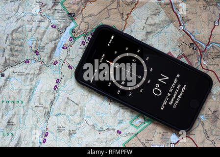 An iPhone 7 with a compass application shown with a topographic map of a portion of the Adirondack Mountains to assist in navigation in the wilderness - Stock Image