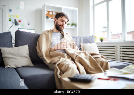 Sick man wrapped into blanket sitting on sofa in front of table with papers while staying at home - Stock Image