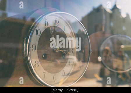 An abstract reflection of the life of the city with people and buildings in the antique clock behind the glass on a summer day - Stock Image