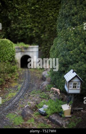 A miniature tableau of a railroad tunnel and a mountain lion, at the Oregon Garden in Silverton, Oregon, USA. - Stock Image