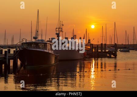 The sun rises over fishing boats and pleasure craft in Vineyard Haven Harbor in Tisbury, Massachusetts on Martha's Vineyard. - Stock Image