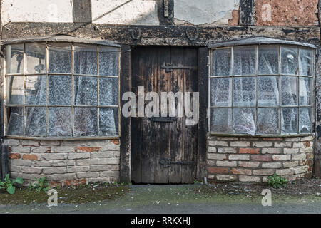 Leominster, Herefordshire, UK. Horseshoes nailed over the door of a derelict cottage with old bow windows, in a quiet back street of this English town - Stock Image