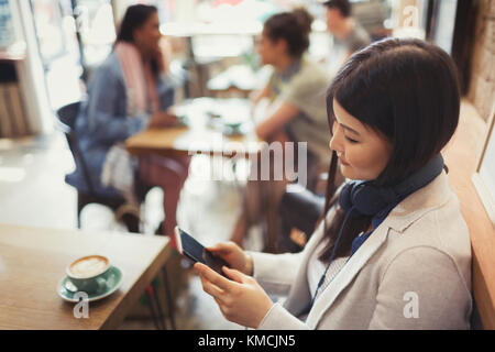 Young woman with headphones texting with cell phone and drinking coffee at cafe table - Stock Image