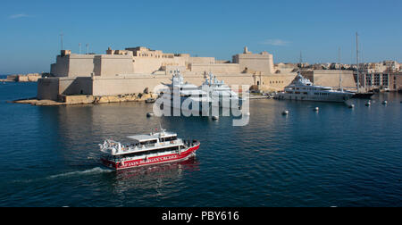 Tour boat passing by Fort St Angelo in the historic Grand Harbour of Malta, Europe - Stock Image