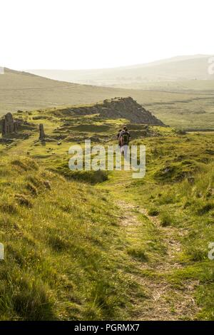 Figures hike a trail in Dartmoor National Park at dusk - Stock Image