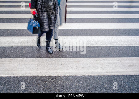 two unrecognizable persons in black shoes cross wet street after rain on crosswalk, red umbrella, parallel lines - Stock Image