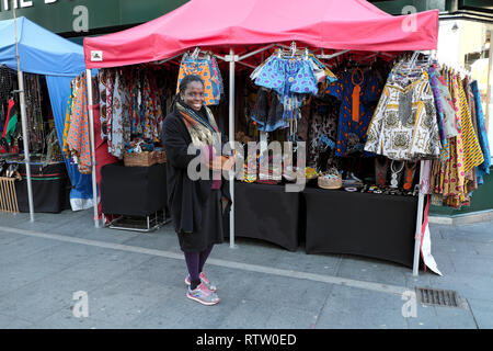 A smiling woman selling African textiles, clothing and jewellery at a street market stall on Brixton Road in Brixton South London UK  KATHY DEWITT - Stock Image
