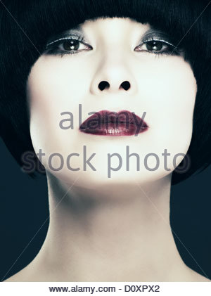 Young woman with black bob looking at camera, low angle - Stock Image