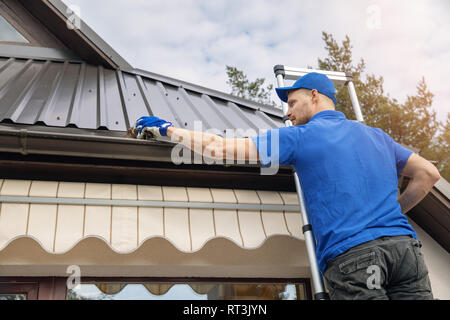 man standing on ladder and cleaning roof rain gutter from dirt - Stock Image