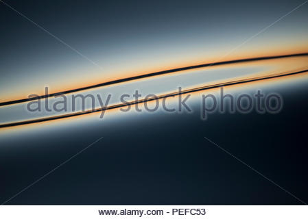 Sunset reflecting on the calm waters. - Stock Image