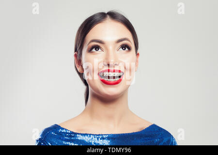 Portrait of happy beautiful woman in braces on white background. Pretty girl with braces on teeth smiling - Stock Image
