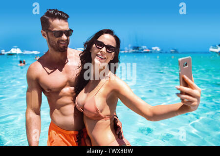 Attractive, young couple taking a selfie during asian vacation - Stock Image