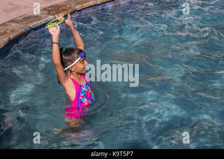 1, one Hispanic girl, playing in swimming pool, swimming pool, freshwater swimming pool, Castro Valley, Alameda - Stock Image