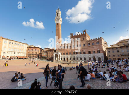 Tourists in the Piazza Del Campo, with the Palazzo Pubblico and Torre del Mangia,  Siena Italy Europe - Stock Image