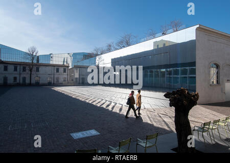 Two young people walking across one of the courtyards of Fondazione Prada, exterior, Milan, Italy - Stock Image