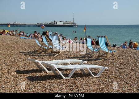 Brighton, UK - September 1 2018: People bask in the sun on the pebbles beach at ​Brighton​ on 1​ September 2018.   The Pier, in the central waterfront section, opened in 1899 houses amusment rides as well as food kiosks .Credit: David Mbiyu Credit: david mbiyu/Alamy Live News - Stock Image