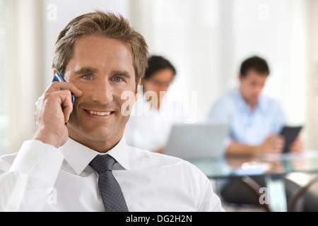 Male mobile phone office desk looking camera - Stock Image