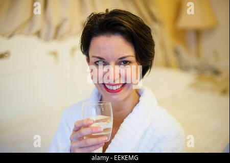 Attractive white woman with stylish short hair looking healthy and happy wearing a white spa robe drinking a glass - Stock Image