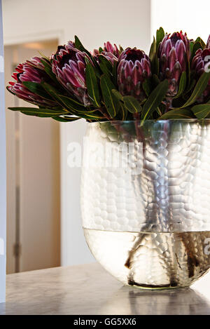Flowers in glass vase on table - Stock Image