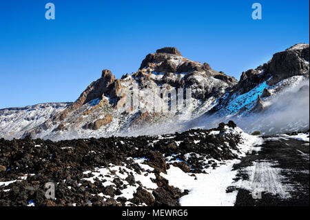 Patches of snow and thin misty clouds in a crisp morning in Teide National Park, Tenerife, Canary Island - Stock Image