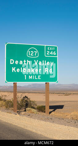 Road distance sign showing exit for Death Valley in Mojave desert, on the Interstate to Las Vegas, California, USA - Stock Image