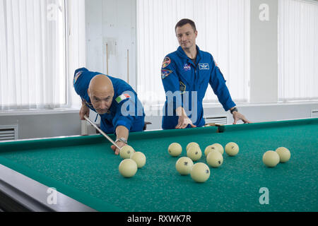 International Space Station Expedition 59 backup crew members Luca Parmitano of the European Space Agency (left) and Drew Morgan of NASA (right) take a moment from pre-launch training for a game of billiards at the Baikonur Cosmodrome March 7, 2019 in Baikonur, Kazakhstan. Expedition 59 crew: Christina Koch of NASA, Alexey Ovchinin of Roscosmos, and Nick Hague of NASA will launch March 14th onboard the Soyuz MS-12 spacecraft for a six-and-a-half month mission on the International Space Station. - Stock Image
