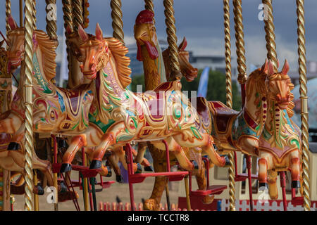 A traditional Fairground carousel with painted horses - Stock Image