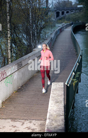 Young woman running along canal path - Stock Image