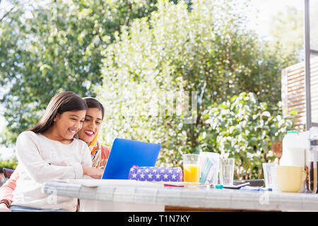 Smiling mother and daughter using laptop at table - Stock Image
