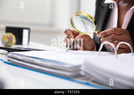 Photo Of Businessperson Examining Bill Through Magnifying Glass - Stock Image