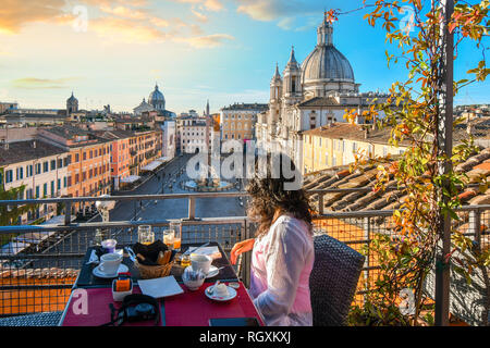 A woman enjoys view of Rome, Italy and the Piazza Navona as she finishes her breakfast from a rooftop terrace of a luxury hotel early summer morning - Stock Image