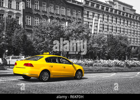 Yellow taxi parked on city street. Black and white. Selective color effect - Stock Image
